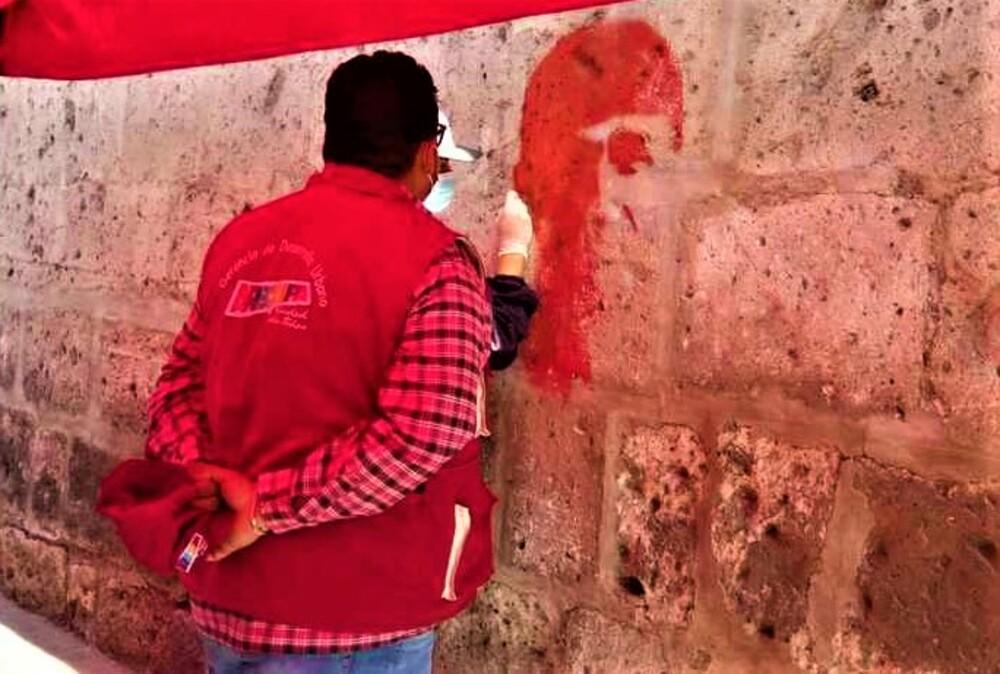 Remoción de imágenes pintadas con spray por simpatizantes de Universitario en muros del monasterio de Santa Catalina, Arequipa.